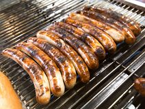 Bratwursts being grilled on an outdoor BBQ grill. Bratwurst sausages being grilled on an outdoor BBQ grill Royalty Free Stock Image