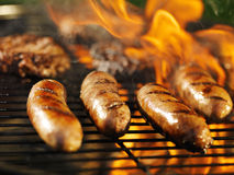 Bratwursts cooking on flaming grill