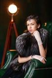 Braunäugiges Mädchen in einer Pelzweste und Handschuhe mit Zusatz auf seinem h Lizenzfreies Stockfoto