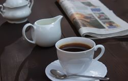 Concept coffee break. On the braun wooden table are cap with saucer and spoon, newspaper, sugar bowl and jug with milk - concept coffee break stock image