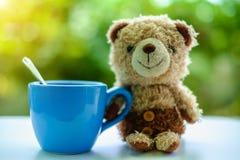 Braunbärpuppe, die mit einem Tasse Kaffee sitzt Stockfoto