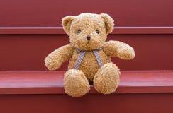 Braune Farbe des TEDDYBÄREN, die auf rotem Treppenhaus sitzt Lizenzfreies Stockfoto