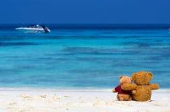 Braune Farbe von zwei TEDDYBÄREN, die auf dem schönen Strand mit b sitzt Stockbilder