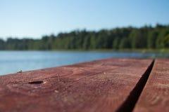 braune hölzerne Planken gegen blauen Himmel und Wasser und grüner Wald und Schilfe Stockbild
