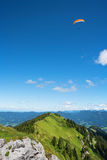 Brauneck mountain peak with circling paraglider. Bright blue sky Royalty Free Stock Images