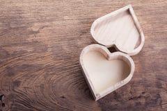 Brauner hölzerner Kasten des Herzens auf hölzernem Hintergrund, abstrakte Liebe Lizenzfreies Stockfoto