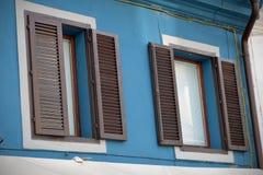 Braunes Fenster zwei auf der blauen Wand Lizenzfreie Stockfotografie