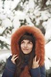 Braunhaariges Mädchen in der Haube mit Pelz lächelnd auf einem Hintergrund von schneebedeckten Bäumen Lizenzfreies Stockfoto