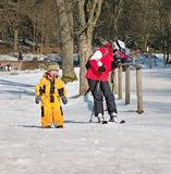Braunlage, Germany - February 15, 2015: Llittle boy with a pacifier and in a sporty ski suit is crying. Near is his mother with royalty free stock photo