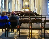 Braunschweig, Germany, November 4., 2018: Older couple sitting at the edge of the last row on the chairs of a Christian church.  royalty free stock photo