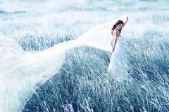 Braut auf dem blauen Gebiet mit wellenartig bewegendem Gewebe Stockbild