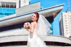 Braut auf dem Hintergrund des neuen Gebäudes stockfotografie
