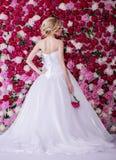 Braut auf dem Pfingstrosenblumenhintergrund Stockbilder