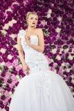 Braut auf dem Pfingstrosenblumenhintergrund Stockfotografie