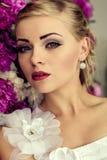 Braut auf dem Pfingstrosenblumenhintergrund Stockfoto