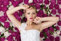 Braut auf dem Pfingstrosenblumenhintergrund Lizenzfreie Stockfotos