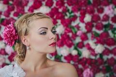 Braut auf dem Pfingstrosenhintergrund Lizenzfreie Stockfotografie
