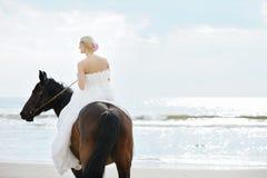 Braut auf einem Pferd durch das Meer Stockfotografie