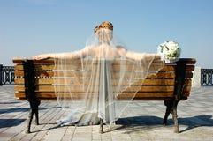 Braut auf einer Bank Stockbild
