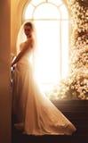 Braut auf Treppe nähern sich archwindow mit Rosen Stockfotografie