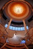Braut auf Treppen mit großem Leuchter über ihr lizenzfreies stockfoto