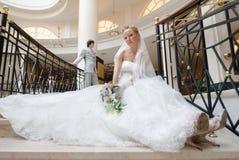 Braut auf Treppenhaus. Auf Hintergrund ist Bräutigam Stockfotografie