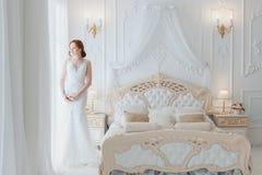 Braut betrachtet heraus das Fenster dem Bräutigam lizenzfreie stockfotografie