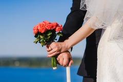 Braut, Bräutigam, Blumenstrauß gegen Hintergrund von Fluss lizenzfreies stockbild
