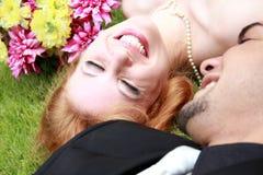 Braut-Bräutigam, der auf dem Gras liegt Lizenzfreie Stockfotos