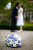 Braut-Bräutigam Kiss mit Blumen Lizenzfreie Stockfotografie