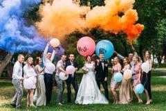 Braut, Bräutigam und Gäste draußen stockfotografie