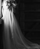 Braut in der Hochzeitskleiderhölzernen Scheune, die am Fenster wartet Stockfoto
