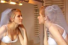 Braut in der weißen Wäsche, die im Spiegel schaut Lizenzfreie Stockbilder