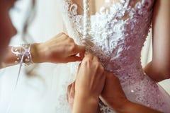 Braut des jungen Mädchens im Hochzeitskleid wartet auf den Bräutigam Freundin hilft, ein Kleid zu befestigen lizenzfreie stockbilder