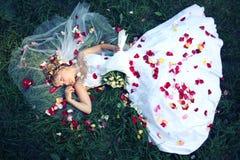 Braut, die auf dem Gras und den rosafarbenen Blumenblättern liegt Stockfotografie