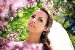 Braut, die auf dem Hintergrund der Blumen aufwirft lizenzfreie stockbilder