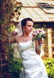 Braut, die auf dem Hintergrund der Blumen aufwirft stockfoto