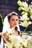 Braut, die auf dem Hintergrund der Blumen aufwirft stockfotos