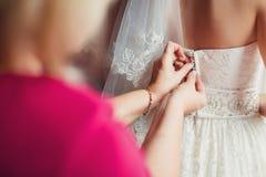 Braut, die auf ein Hochzeitskleid sich setzt Lizenzfreies Stockbild