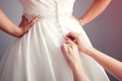 Braut, die auf ein Hochzeitskleid sich setzt Lizenzfreie Stockbilder