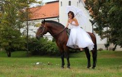 Braut, die auf einem Pferd sitzt Lizenzfreie Stockfotografie