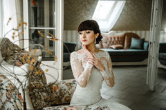 Braut, die auf einem Sofa in einem schönen Raum sitzt Stockfotografie