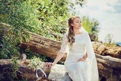 Braut, die auf einem Stein sitzt stockfotografie