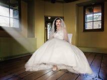 Braut, die auf einem Stuhl in einem Raum sitzt Lizenzfreie Stockfotos