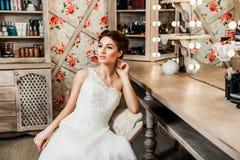 Braut, die auf einem Stuhl nahe dem Spiegel sitzt Lizenzfreies Stockfoto