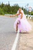 Braut, die auf einer Straße hitching ist Stockfotografie