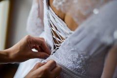 Braut, die auf Hochzeitskleid mit den Verkäufen behilflich versucht Lizenzfreies Stockbild