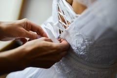Braut, die auf Hochzeitskleid mit den Verkäufen behilflich versucht Stockfotografie