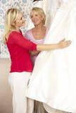 Braut, die auf Hochzeitskleid mit den Verkäufen behilflich versucht Stockbild