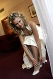 Braut, die auf Hochzeitsschuhe sich setzt Lizenzfreies Stockfoto